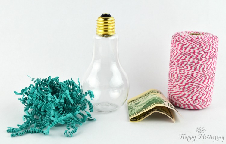 Blue shredded paper, clear plastic craft light bulb, $50 bill and red baker's twine on a white background