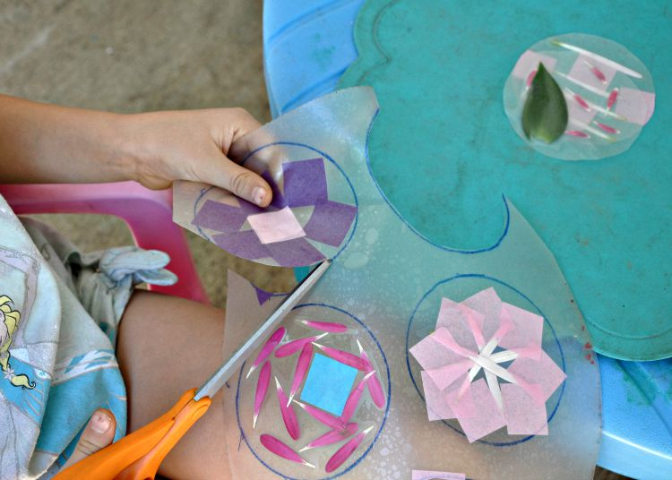 Zoe cutting suncatchers out of the contact paper that has been pressed together