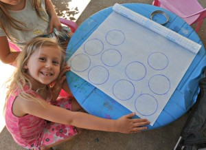 Circles traced on contact paper with the girls sitting at a blue plastic kids table