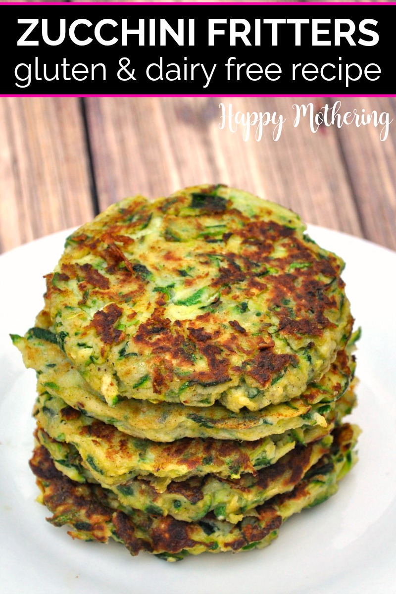 Top view of zucchini fritters stacked on white ceramic plate on wood table