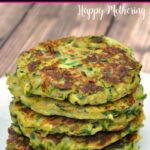 Five zucchini fritters stacked on a white plate set on a brown wood table