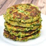 Close up of stack of 5 gluten free zucchini fritters on a white plate set on a brown wood table