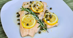 Two perfectly poached salmon filets on a dinner plate, garnished with lemon, capers and rosemary.