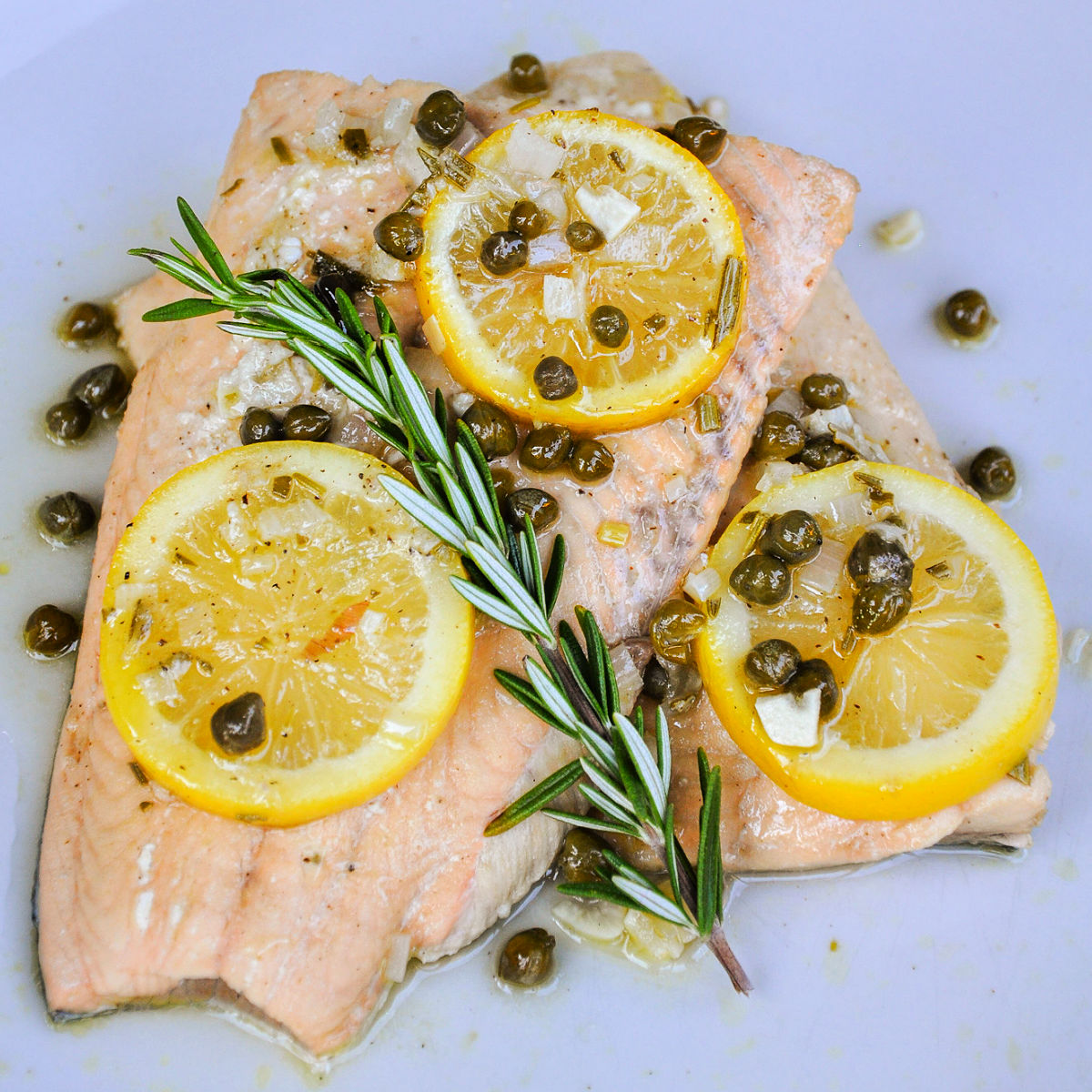 Two poached salmon filets garnished with lemon slices, capers and a sprig of fresh rosemary.