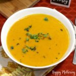 Bowl of butternut squash soup topped with fresh thyme