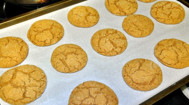 Fresh baked gluten free gingersnaps on a cookie sheet lined with parchment paper