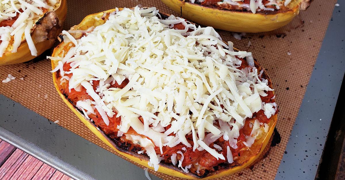 Grated mozzarella cheese spread over top of spaghetti squash lasagna boats.