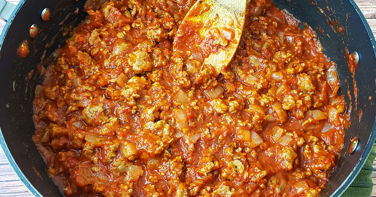 Meat sauce being cooked in pan.