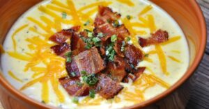 Bowl of Instant Pot Cauliflower Soup topped with bacon, cheddar and chives