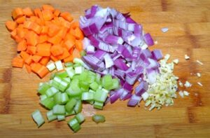 Carrots, red onion, celery and garlic chopped on a bamboo cutting board