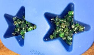 Green crayon pieces and silver glitter in a blue star shaped silicone mold
