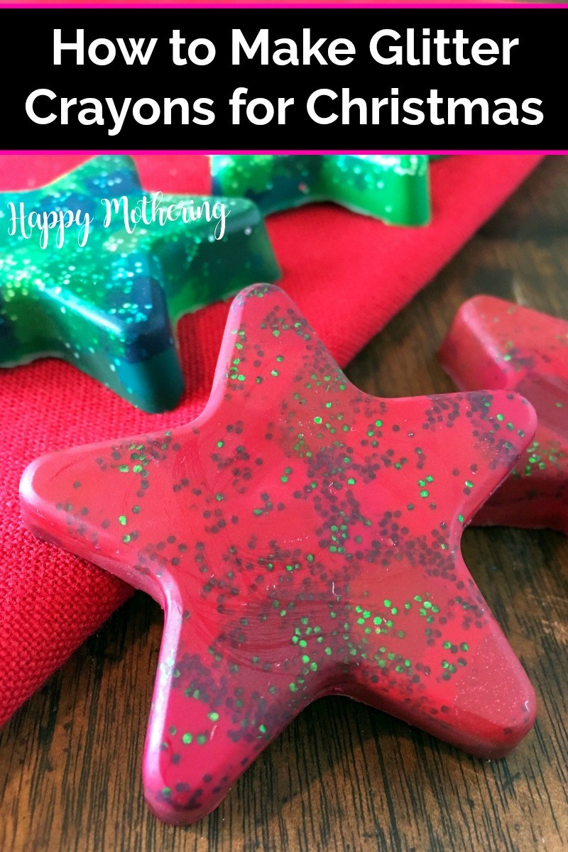 Two red and two green star shaped glitter crayons on a wood table with red silicone mold