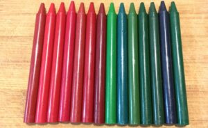 Unwrapped red and green crayons on a bamboo cutting board