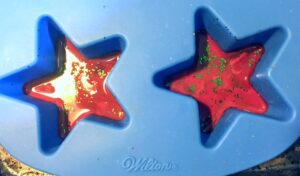Melted red crayon with green glitter in a blue star shaped silicone mold