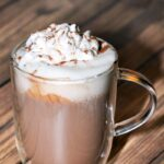 Homemade hot chocolate in clear glass mug topped with whipped cream and cocoa powder