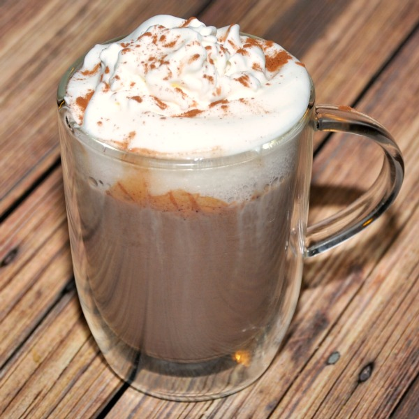 Clear glass mug of homemade hot chocolate topped with whipped cream and cocoa powder