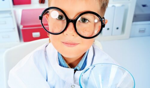 Kid with oversized glassed in lab coat with beaker