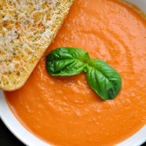 Close up of cream of tomato soup in a white bowl with basil and sourdough toast garnishes