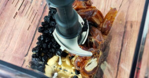 Dates, cashews, and dried blueberries in blender pitcher.