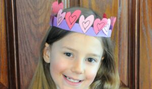 Close up of Zoe wearing the paper crow of hearts she crafted for Valentine's Day