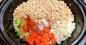 Navy beans and spices added to slow cooker with veggies.