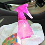 Pink plastic spray bottle of homemade upholstery cleaner on white towel next to sponge on passenger side car seat