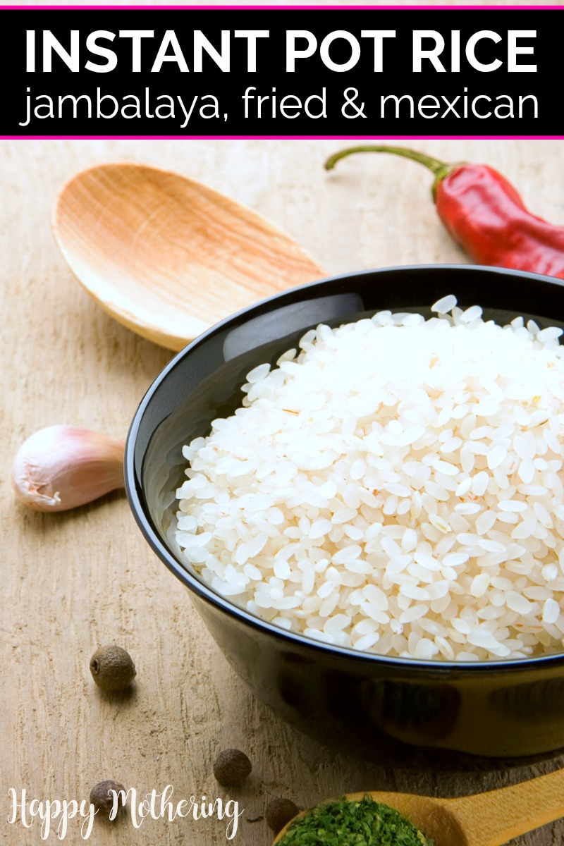 Black bowl of uncooked white rice on a wood surface with a wood spoon, red pepper, garlic clover and peppercorns