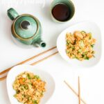 Overhead view of two bowls of fried rice with chopsticks and a tea kettle with two cups on a white table