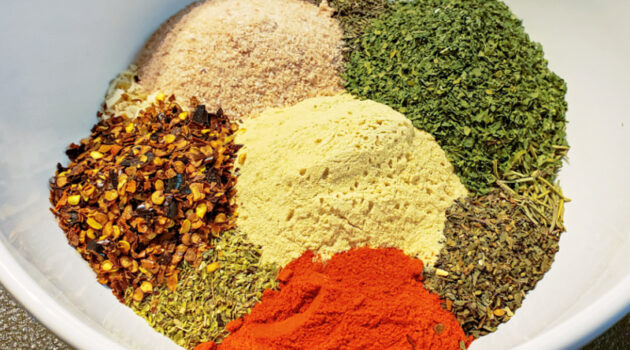 Ingredients for homemade Italian seasoning in small piles in a white bowl.