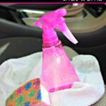 Pink spray bottle of DIY upholstery cleaner on a car seat with a sponge