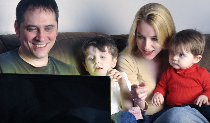 Family of four sitting on a couch looking at a computer screen