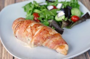Jalapeno Popper Stuffed Chicken breast on a white plate with a green salad