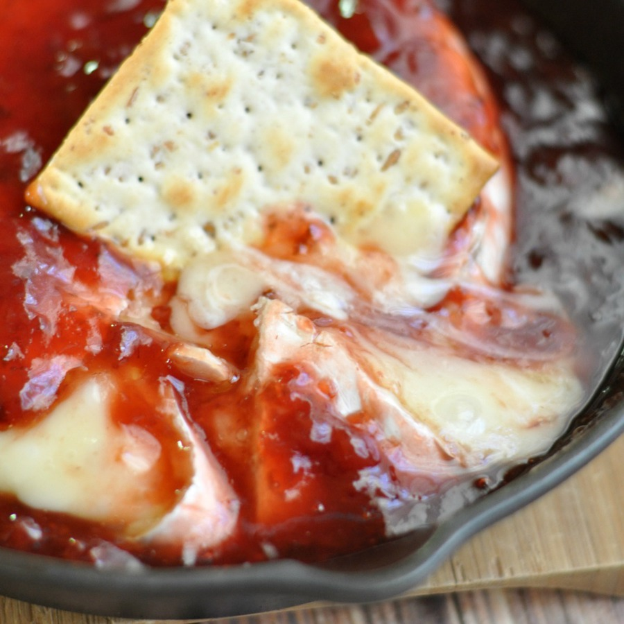Plain gluten free cracker dipped into hot baked brie with red pepper jam