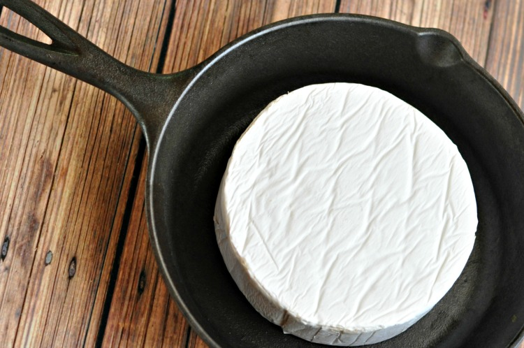 Cold brie wheel in a cast iron skillet on a brown wood table