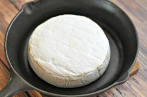 Brie wheel that was baked in a cast iron skillet until it's melted sitting on a wood table.