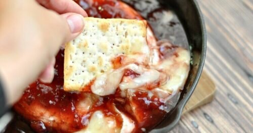 Sweet and spicy baked brie in a cast iron skillet being dipped into with a wheat cracker
