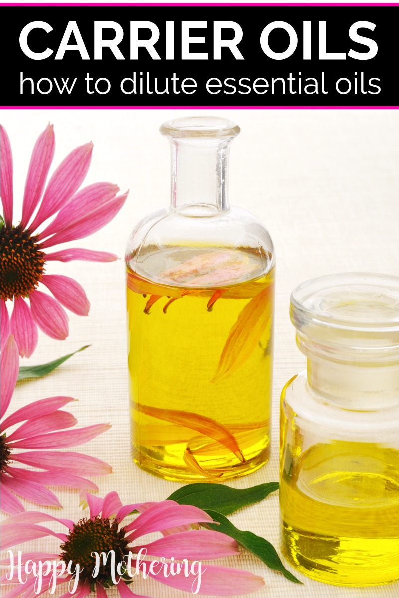 Two clear glass bottles of infused oil with pink coneflowers spread next to them on a white counter