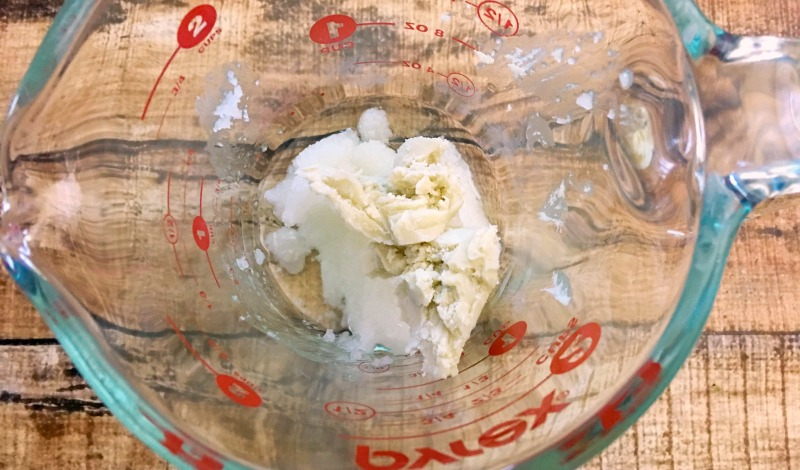 Shea butter and coconut oil in a glass measuring cup on a brown wood table