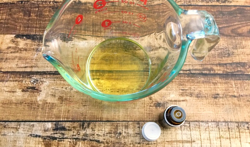 Butter and oil melted in a glass measuring cup with a bottle of essential oils next to the cup.