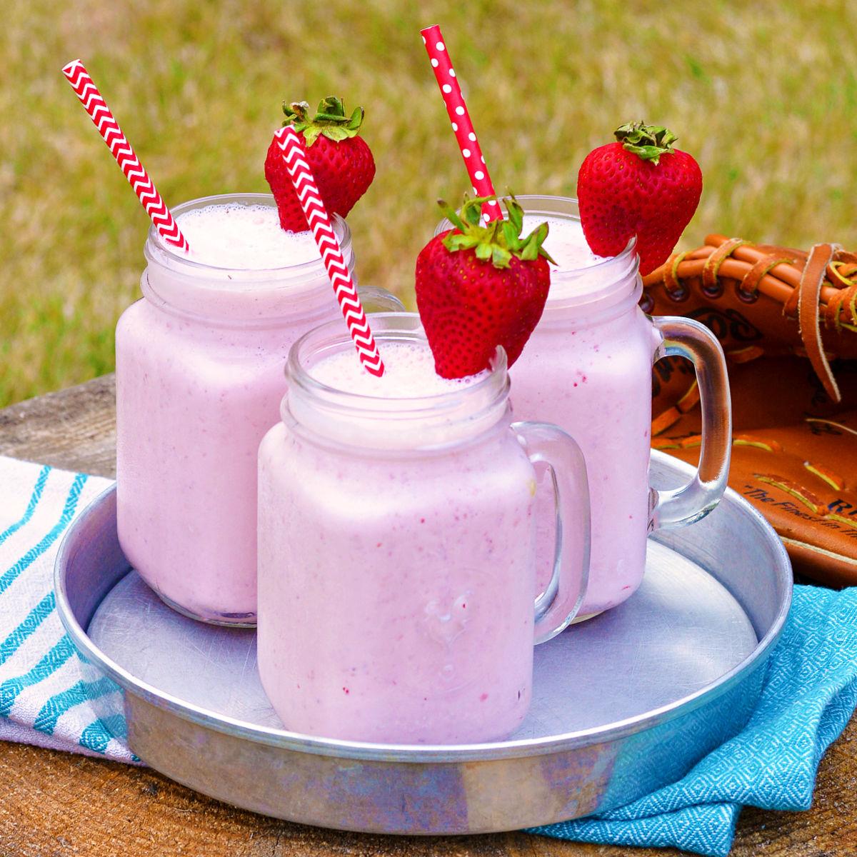 Three strawberry milkshakes on a silver serving tray