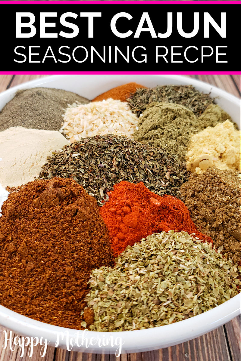 White mixing bowl filled with piles of dried spices and seasonings used to make cajun seasoning