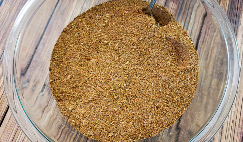 Clear glass mixing bowl of homemade cajun seasoning being mixed with a spoon on a wood table