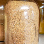 Quart sized mason jar of homemade Cajun Seasoning in a spice cabinet