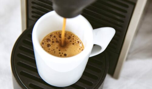 White coffee mug being filled by single serve coffee maker