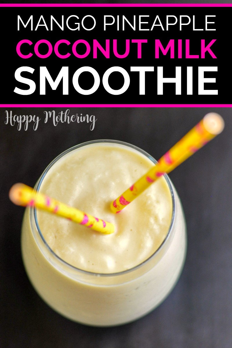 Overhead view of Mango Pineapple Coconut Milk Smoothie with two paper straws on a dark wood table
