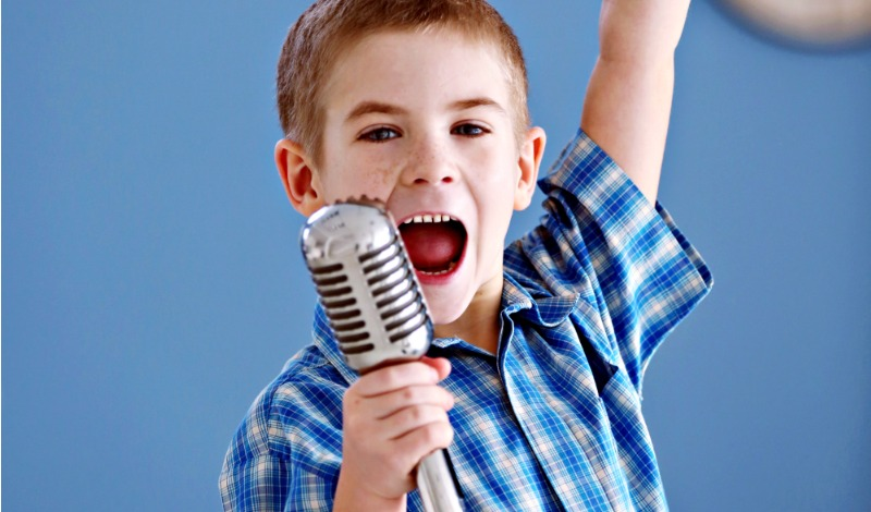 Boy singing into a microphone with a blue wall behind him