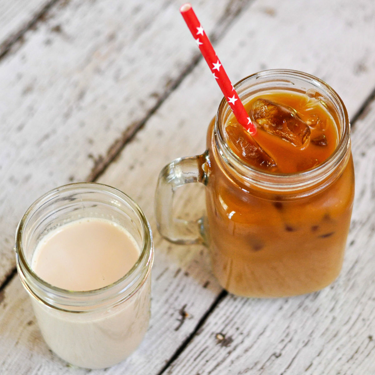 Copycat Starbucks Vanilla Sweet Cream Cold Brew Coffee in a pint sized glass mason jar next to an 8 ounce jar of coffee creamer on a white distressed table