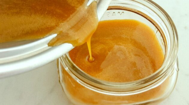 Salted caramel sauce being poured from the pan into a squat glass mason jar on a white counter.