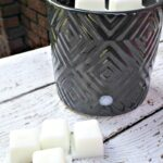 Black wax warmer filled with coconut oil wax melts on white wood table and brick background