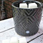 Black wax warmer on white wood table in front of brick wall
